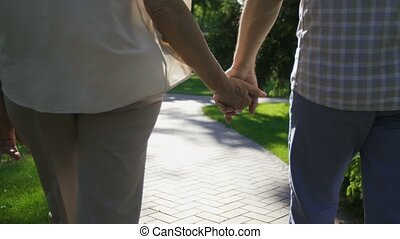 Closeup senior couple holding hands during a walk