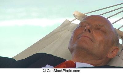 closeup senior manager sleeping in hammock