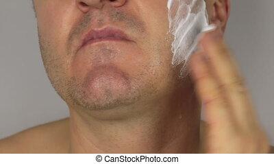 Closeup  shave a man, use shaving foam on face