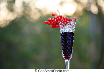 Closeup shoot of the 2 glasses of wine with the bunch of viburnum berries