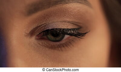 Closeup shooting on green eye of young woman looking around....