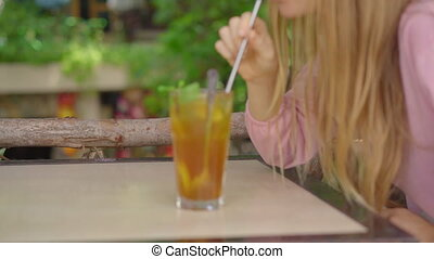 Closeup shot. In a cafe, a young woman uses her own reusable metallic straws instead of a single-use plastic drinking straw. Concept of reducing the use single plastic.