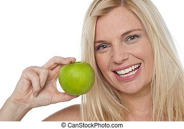 Closeup shot of a cheerful woman holding an apple