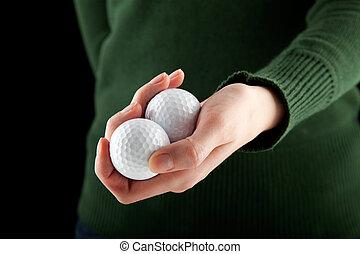 closeup shot of a female hand holding two golf balls