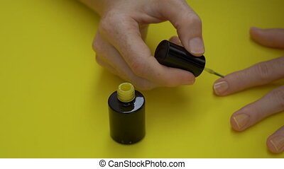 Closeup shot of a girl that paints her nails in yellow on a...