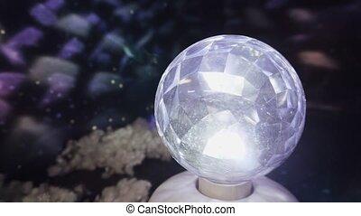Closeup shot of a led garland, festive disco ball rotates in the dark.