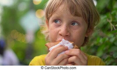 Closeup shot of a little boy eating a tasty pancake on a...
