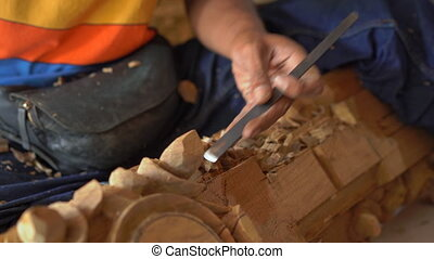 Closeup shot of a master craftsman doing traditional wood ...