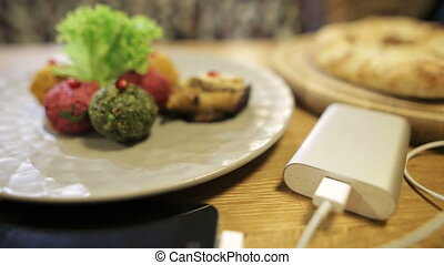 Closeup shot of a portable battery charger for mobile phone and georgian dish pkhali. Easy way to have cellphone working any time. Smartphone charging from a USB power bank. The indicator flashes