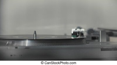 Needle in the groove of a record as it slowly spins vintage and retro music