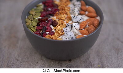 Closeup shot of a smoothie bowl with papaya, dragon fruit, granola, dried cherry, and pumpkin seeds. Healthy breakfast concept