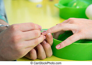 Closeup shot of a woman in a nail salon receiving a manicure by a beautician with nail file. Woman getting nail manicure. Beautician file nails to a customer