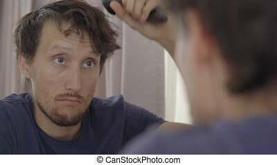 Closeup shot of a young man in mandatory quarantine. He stays in one room for two weeks. He did not shave for a long time, he needs a haircut. Sits by the mirror and looks at himself. He is stressed and upset. Staying in quarantine concept. Concept of the second wave of Covid-19. Loneliness and ...