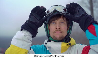 Closeup shot of a young man wearing a helmet with a snowboard in a mountain resort. He puts on his snow googles. Winter holidays concept. Slowmotion shot