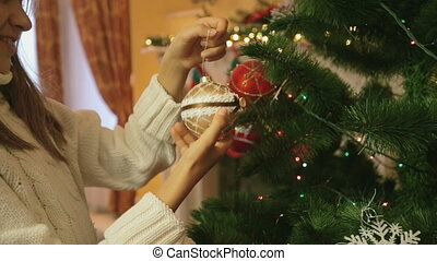 Closeup shot of beautiful girl hanging golden bauble on Christmas tree