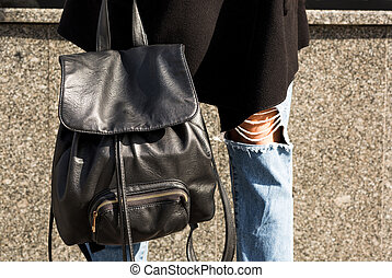 Closeup shot of black leather backpack at the woman's legs