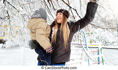 Closeup shot of blond woman with her cute son in jacket and hat playing with snow covered tree on the playground in the Park