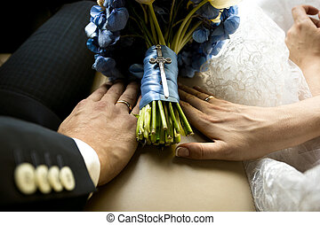 bride and groom holding hands on wedding bouquet at car