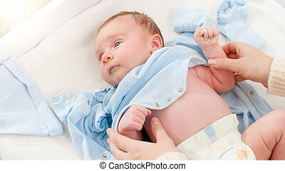 Closeup shot of caring mother undressing her little 1 months old baby boy lying on changing table. Concept of babies and newborn hygiene and healthcare. Caring parents with little children.