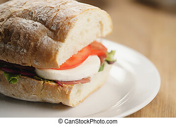 closeup shot of ciabatta sandwich with speck, mozzarella and vegetables