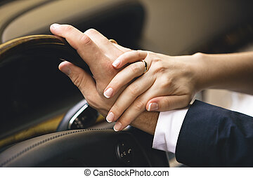elegant woman holding hand on men hand while he drives a car