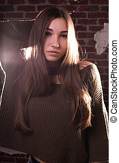 Closeup shot of fashionable brunette woman wears oversize sweater, posing on a brick wall background