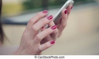 Closeup shot of female hands holding smartphone, typing text...