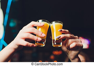 Closeup shot of friends toasting with cocktails. Young people drinking at aperitif. Shallow depth of field with focus on friends hand toasting juice glass. Close up of hands holding a cocktail glass.