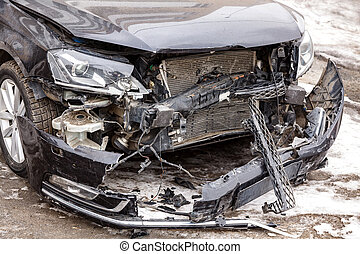 Closeup shot of front part of a black car damaged in accident on the road