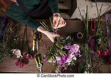 closeup shot of hardworking hands creating beauty from flowers. creative mess on florist's desk