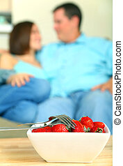 closeup shot of healthy fruits strawberry with young couple talking on the background