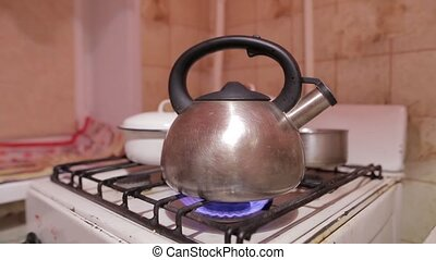 Closeup shot of kettle on natural gas flame. Tea drinking at...