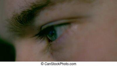 Closeup shot of man's eye surfing internet at night