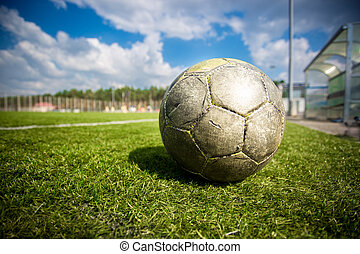 old soccer ball on grass field at sunny day