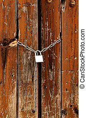 Closeup shot of padlock on the old wooden gates