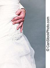 closeup shot of wedding dress and groom hand