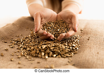 Closeup shot of woman holding mound of golden nuggets in...