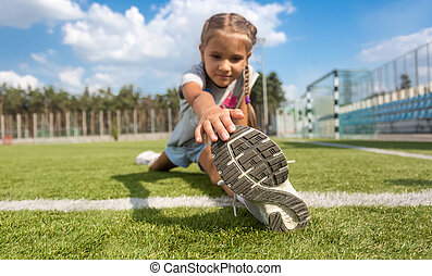 young girl stretching legs on soccer field at sunny day