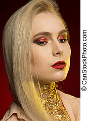Closeup shot of young model with bright makeup. Red and yellow studio light