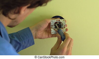Closeup shot of young professional electrician doing socket ...