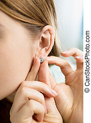 Closeup shot of young woman wearing erring with diamond -...