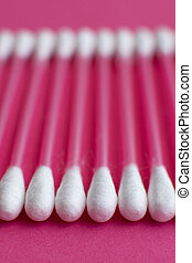 Closeup side view on cotton buds laid in a horizontal line on pink background