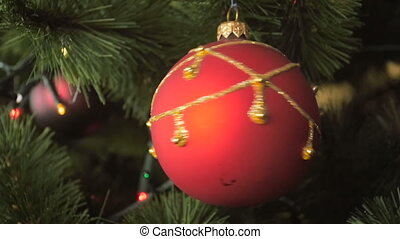 Closeup slow motion footage of beautiful red bauble spinning on decorated Christmas tree