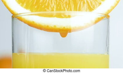 Closeup slow motion footage of droplet slowly falling in glass of orange juice