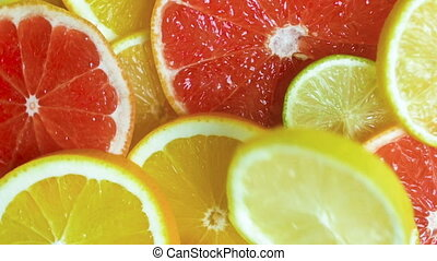 Closeup slow motion footage of falling orange, lemon and...