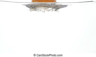 Closeup slow motion footage of fresh ripe grapefruit falling and splashing in clear cold water against white background