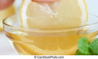 Closeup slow motion footage of hand dipping lemon slice in...
