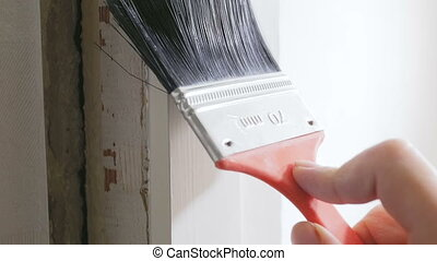 Closeup slow motion footage of hand holding paintbrush and...