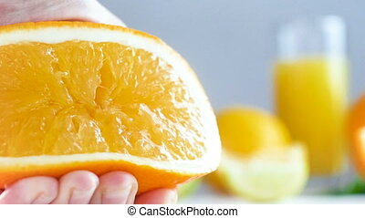 CLoseup slow motion footage of hand squezing orange. Juice...