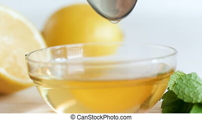 Closeup slow motion footage of honey slowly dripping from spoon in glass jar on white wooden table